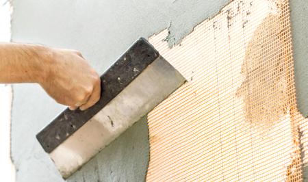ade: The process of putty the walls with a large spatula Stock Photo