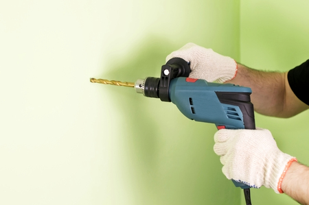 drills: The process of drilling using electric drills on a background of green wall