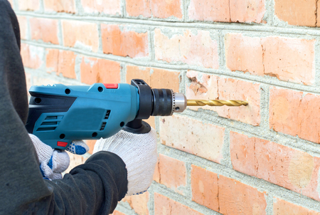 drills: The process of drilling using electric drills on a background of a brick wall