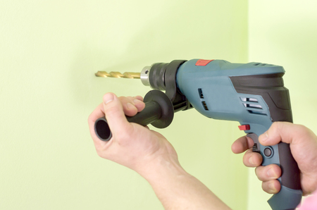 drills: Holding  in hands Electric drills  on a background of green wall