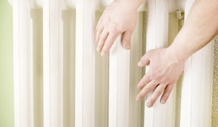 touching hands: Touching hands to sections of cast iron radiator of white color
