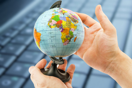 extent: Political globe in the hands on the background of laptop keyboard Stock Photo