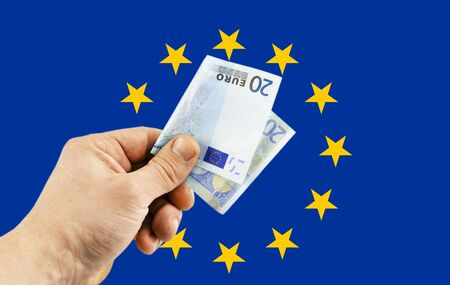 denomination: Banknote in denomination of 20 euro in  hand against the background of the flag of the European Union