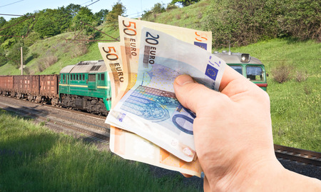 cross ties: The euro in his hand on a background of green train under the open sky