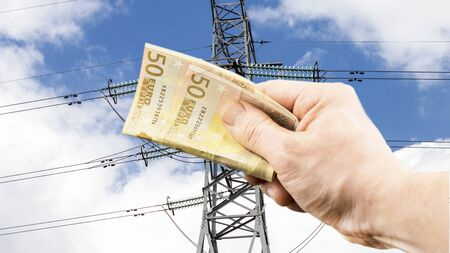 against the current: The euro in hand on the background of power lines under the open sky