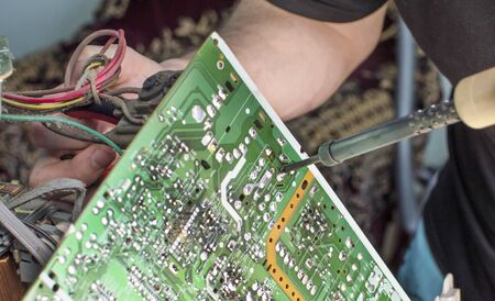 diodes: The process of soldering microcircuit TV using a soldering iron Stock Photo