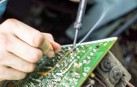 soldering: The process of soldering microcircuit TV using a soldering iron Stock Photo