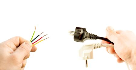 conductor electricity: Various wires and plugs in his hand on a white background