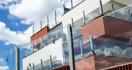 glass fence: Residential building with glass fence on a background of blue sky with clouds Stock Photo