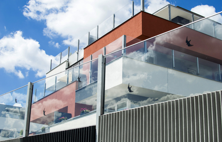 residential building: Residential building with glass fence on a background of blue sky with clouds Stock Photo