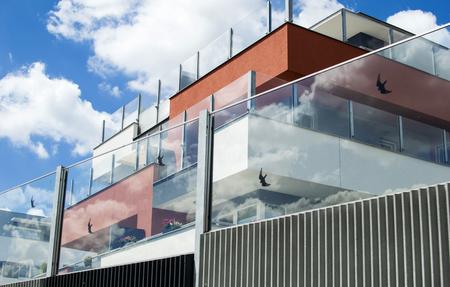 Wohngebäude mit Glaszaun auf dem Hintergrund des blauen Himmel mit Wolken Standard-Bild