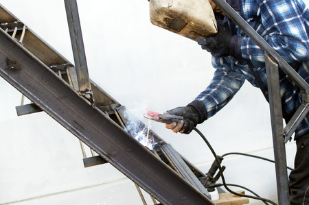 armature: The process of welding metal armature on the background of the white wall Stock Photo
