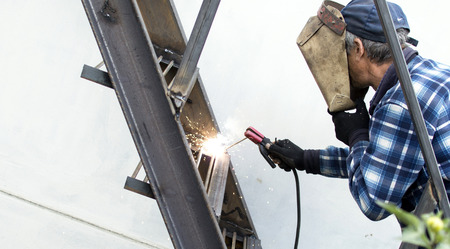 The process of welding metal armature on the background of the white wall Stock Photo