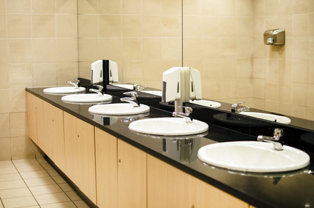 sinks: Sinks with mirrors and soap dispensers in the room toilet Stock Photo