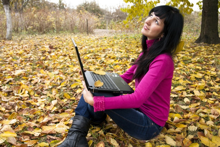 advertizing: The beautiful woman with the laptop in an autumn garden