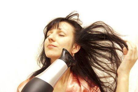 secador de pelo: La mujer el cabello seco el secador de pelo en un fondo blanco