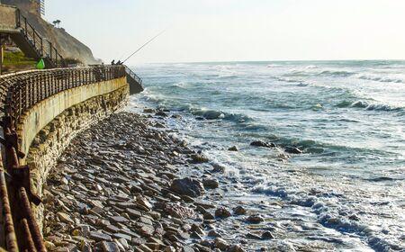 Fisherman on quay sea fishing using fishing rods Stock Photo
