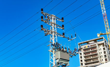 against the current: Metallic support of transmission lines against the sky Stock Photo
