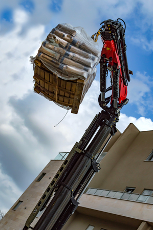 The process of lifting cargo by means of a hydraulic manipulator on the background of a multistory building and a blue sky
