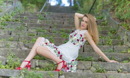 Menina bonita sentada nos degraus de pedra no parque verde