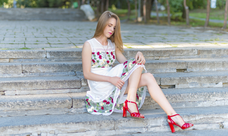 head stones: Beautiful girl sitting on stone steps in the green park Stock Photo