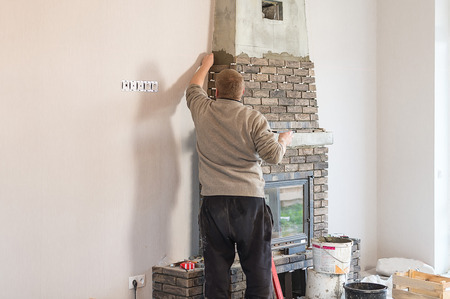 The process of installing the tile on the surface of the fireplace in the house