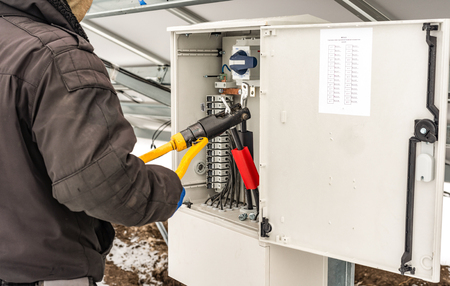 The process of pressing the copper cable tips in the box of connections Фото со стока