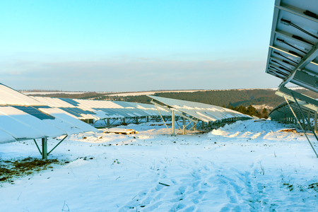 Rows of solar panels are covered with white snow