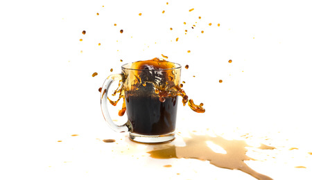 A cup of coffee with splashes in the process of spilling on a white background