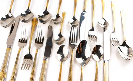 Different chrome-plated cutlery - forks, spoons and knives on a white background Stock Photo