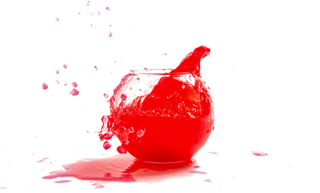 Splashes of red liquid in a glass globular vase on a light background 스톡 콘텐츠