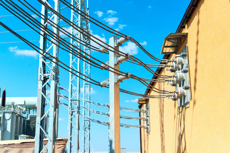 High-voltage aluminum wires coming out of the building of distribution equipment against the background of a blue sky