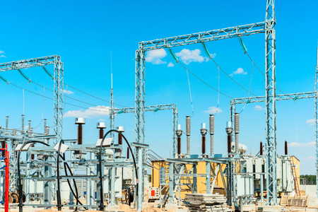 Electric substation with dischargers, vacuum interrupters and high voltage transformers against the background of a blue sky Stock Photo