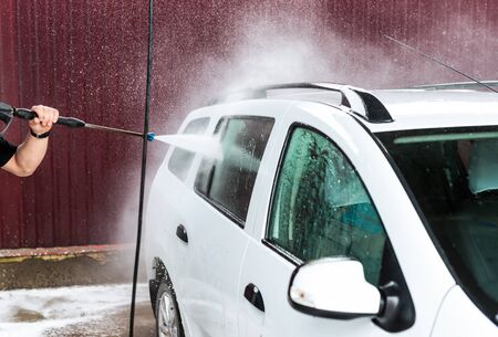 The process of washing a white car using a pressure washer on a self-wash car wash