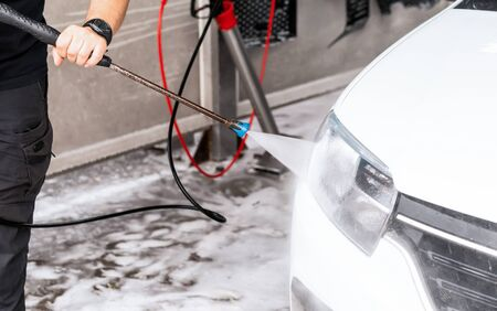 The process of washing the headlights of a car with the help of a pressure washer on a self-wash car wash