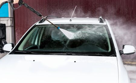 The process of washing the windshield of a car using a pressure washer on a self-wash car wash Stok Fotoğraf