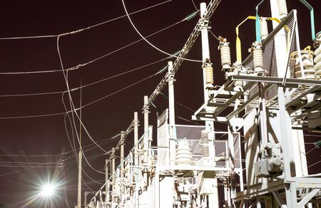 Electric substation with high-voltage equipment - isolators, bearings, transformers, wires, etc. at night Imagens