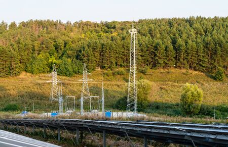 Rows of solar panels on a background of supports and power lines among the forest Фото со стока