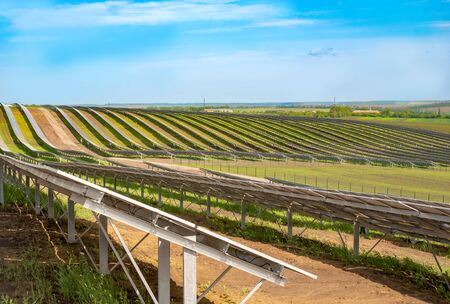 Rows of solar panels on steep hills fields on sky background - rear view Stockfoto