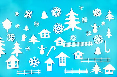 Applique of various Christmas-themed figures cut out of white paper on blue background