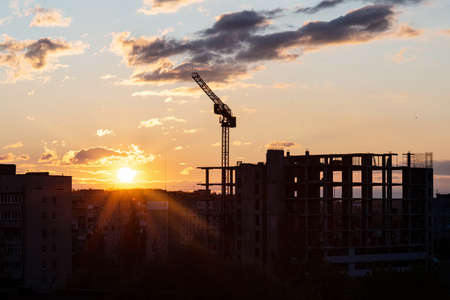 Construction crane and construction of a new high-rise building among the city on a background of sunset
