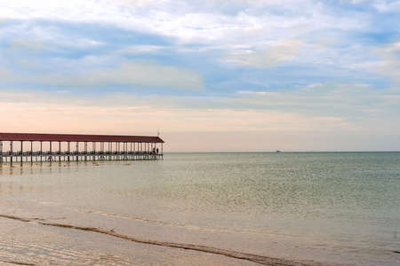 Pier indoor with tables for relaxation by the sea on a background of blue sky with clouds