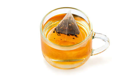 The process of immersing a tea bag in the shape of a pyramid in a transparent glass cup on a white background