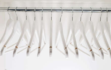 Wooden white clothes hangers inside the closet Standard-Bild