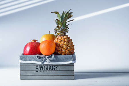 Fresh fruits in grey wooden box with inscription Storage. Stock Photo