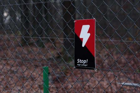 Danger red black sign with lightning on the grille Imagens