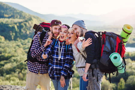 Summer travel concept. Happy friends using paper map near rented car in nature. Happy travelers in mountains on weekend vacation. Beautiful young men and women holding map, exploring location on trip.
