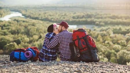 Young couple with backpacks traveling together in mountains. Happy hipster man kissing his girlfriend on the top of mountain at sunset backdrop. Traveling, tourism and relationships concept. Standard-Bild