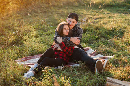 Young man hugs tenderly his pretty girlfriend. Young couple sits on the plaid at green lawn at sunset.