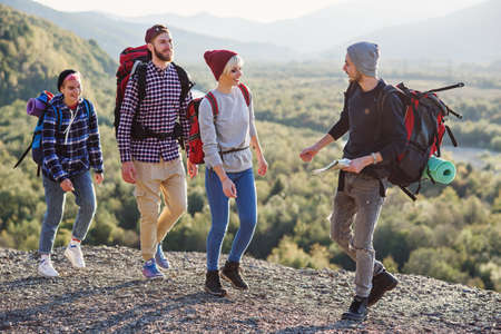 Two hipster couples with backpacks hiking in the mountains during long trip. Happy caucasian group of travelers have an amazing walk trip at the mountains.